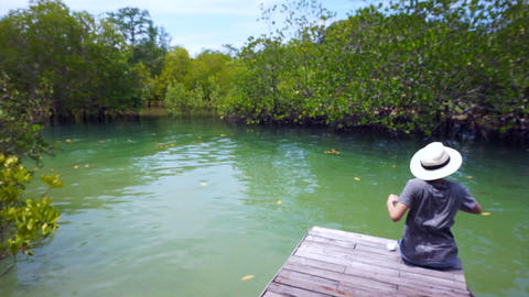 Video of Asian girl wearing hat sits on a small pier next to the Intertidal fore Footage