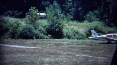 1963: Private airfield airplanes parked in grass dirt hangar Footage