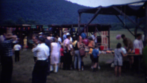 1962: Country fair crowd amusement rides carnival games Footage