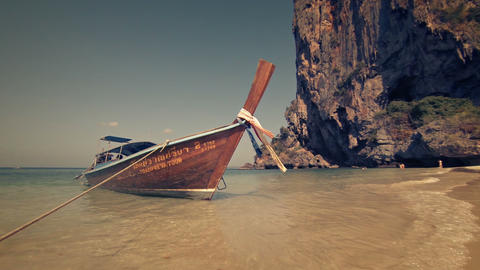 Wooden longtail boat. tied on tropical beach paradise in Thailand. with rocks Footage