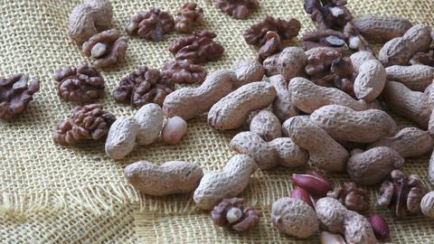 Walnuts, peanuts on yelow background Footage