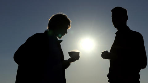 Two young men drink hot tea at a picturesque sunset in 4k Image