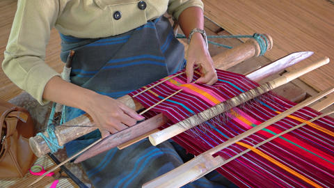 Skilled weaver works colorful patterns into her project in Indonesia Footage