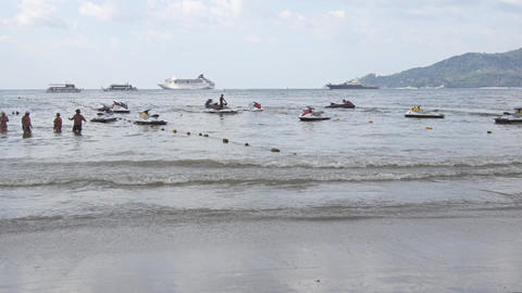 Laborer Parks a Rental Jetski at Anchor while Tourists Swim in the Tropical Sea Footage