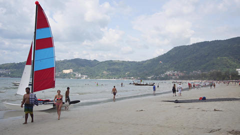 Tiny Catamaran Sailboat for Rent on Crowded Patong Beach Footage