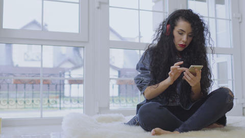 Charming brunette with red lips listen music with headphones and use phone Footage