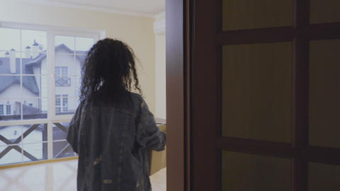 Young woman examines an empty room in a new house Footage