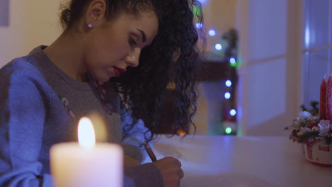 Beautiful woman writes a wish list at the Christmas Footage