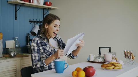 Young happy woman surprised to recieve good news reading letter in the kitchen Footage