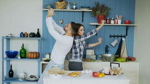 Happy young couple have fun dancing and singing in kitchen while listening to Footage