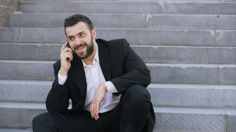 Young bearded business man talking on cell phone making deals sitting on stairs Photo