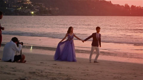 Young bride and groom posing for a professional photographer on the beach Footage