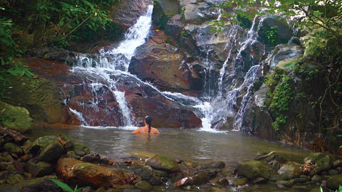A woman bathes in the natural tropical waterfall Footage