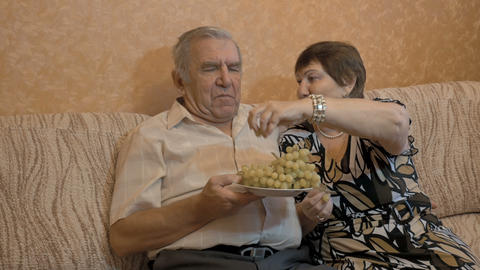 An elderly woman feeds her husband's grapes. They are a happy couple Filmmaterial