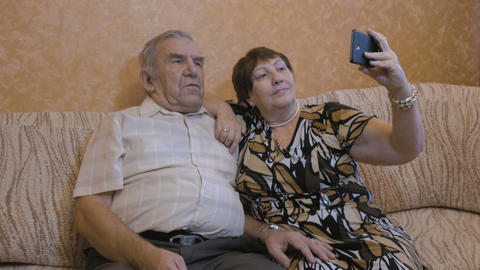 An adult couple makes selfie. Use a smartphone for photos Footage