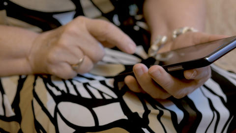 The hands of an elderly woman who dials sms on a smartphone. Close-up Footage