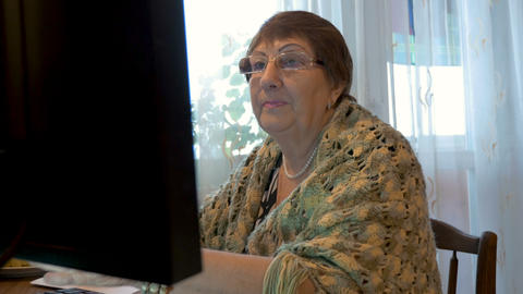 An elderly woman, a grandmother, uses a computer. Studying modern technologies Footage