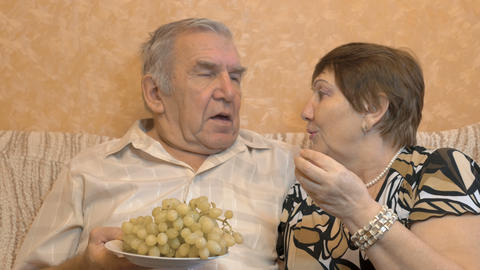 Elderly couple eating grape berries. They feed each other. Happy time Footage