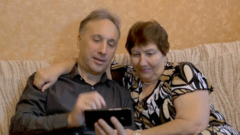 An elderly woman and her adult son are watching photos of their family on a Footage