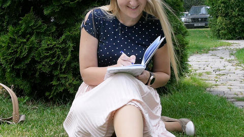 Young woman sitting in park and writing a diary Footage