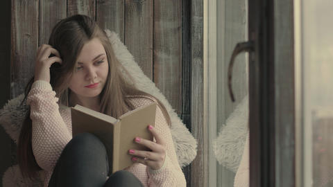 Cute young woman reading book Footage