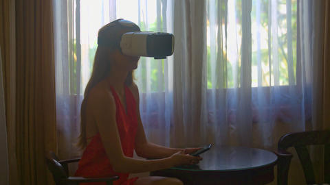 Woman Sits in Virtual Reality Helmet at Window Closeup 영상물