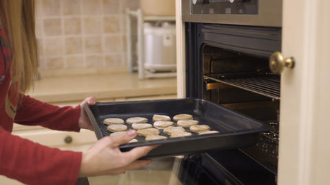 Girl put the baking tray with cookies in oven Footage