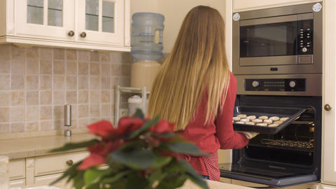 Young girl put the baking tray with cookies in the oven Footage