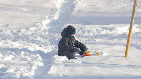Boy playing with toy sitting on snow Footage