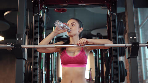 slender sexy girl is drinking water from a bottle in the gym. Sportswoman in Footage