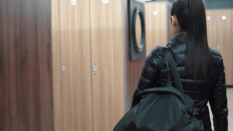 girl in a black jacket and with sports bags comes into the locker room in the Footage