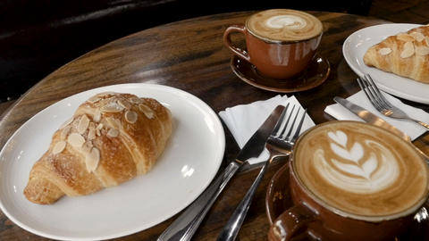 Low angle of latte art and almond croissants on a dark wooden table for a Footage