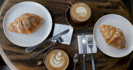 Overhead of two cups of coffee and two pastries from a bakery on a breakfast Live Action
