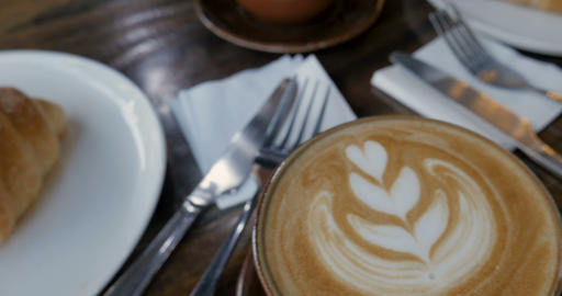 Close up of delicious tulip coffee art and pastry croissant breakfast in a cafe Footage