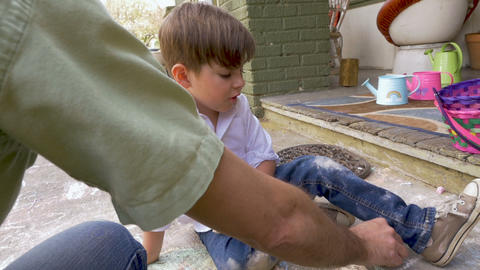 Little cute 4 year old boy watching his father drawing with chalk outside in Footage