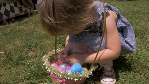 Adorable little 2 - 3 year old girl opening a piece of candy from her Easter Footage