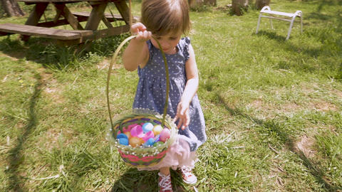 Adorable 2 - 3 year old girl in spring dress holding an easter basket filled Footage