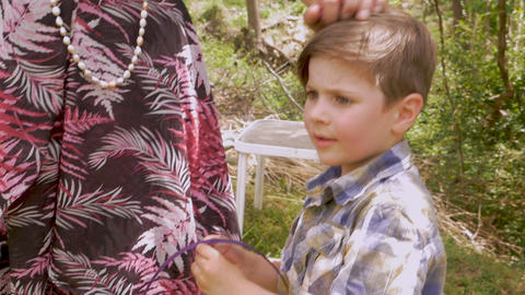 Mother affectionately stroking a young boy's hair that is parted to the side in Footage