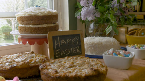 Easter desserts, candies, cookies and a sign that says Happy Easter on a chalk Footage