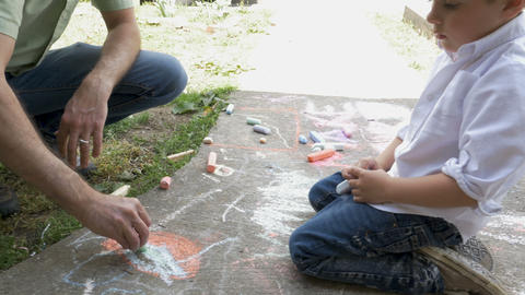 Father and son drawing with chalk on a sidewalk together. The boy is 4 - 5 years Footage