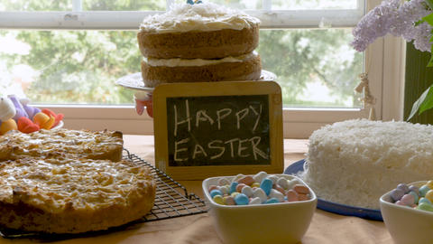 Homemade desserts displayed on a wooden table and a sign that says happy Easter Footage
