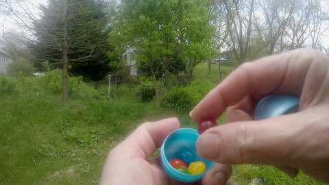 POV of a hand opening up a plastic Easter egg with jelly beans inside while Footage
