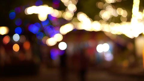Blurred Lights on big trees and people silhouette walking under colourful Lamps  Footage