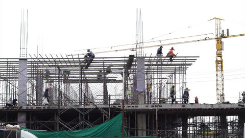 construction and development. Workers working on new building with crane in background Footage