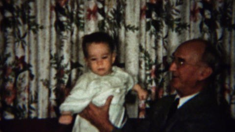 1958: Grandma passes baby to grandpa practice clapping Footage