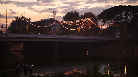 THAILAND, CHIANG MAI, Sunset at the bridge. People launch floating of decorated Footage