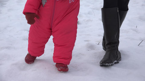 Newborn Baby Girl Walking She's First Steps in a Winter Day. 4K UltraHD, UHD Footage