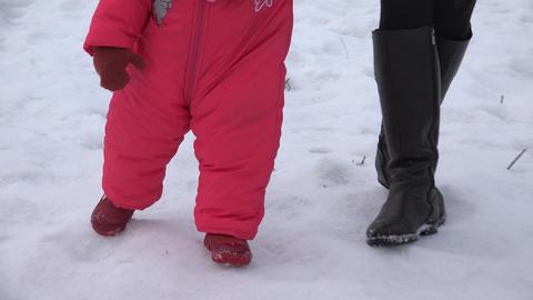 Newborn Baby Girl Walking She's First Steps in a Winter Day. 4K UltraHD, UHD Footage