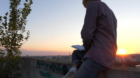 4k - Young man sitting on the roof and reading book at sunset 画像