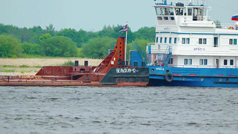 Tug boat pushing an industrial barge on the Volga River Footage